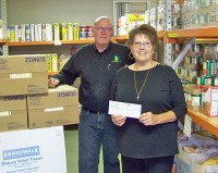 Monkeytown's Kurt Karr presents a donation to Food Pantry's Linda Wood. Credit Vinton Today