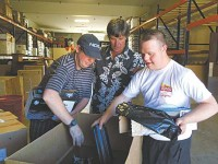 YEI!'s Executive Director Brad Newman (centre) assists YEI! employees Brock Wright (left) and Sky Casley (right) process used toner cartridges at YEI!'s Prescott Valley warehouse for QCOffice's new toner cartridge recycling programme. (Credit: Max Efrein/The Daily Courier)